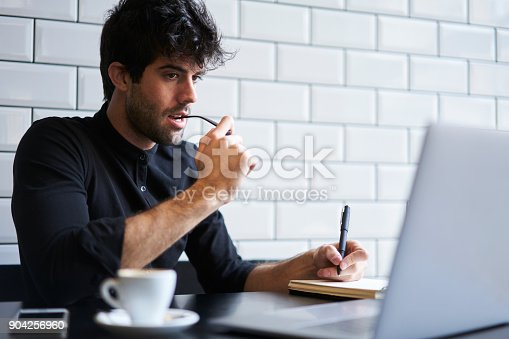 904263506 istock photo Young male businessman with eyeglasses thinking about building plan on future year using free internet connection on computer and noting every step in notebook while drinking coffee in cafe 904256960