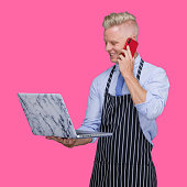 istock Young male butcher standing in front of black background wearing apron and using computer 1246342287