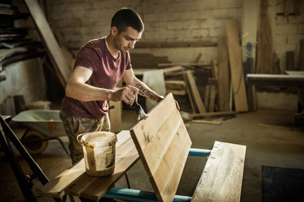 jonge mannelijke timmerman vernis toepassen naar de stuk hout in een workshop. - houtbeits stockfoto's en -beelden