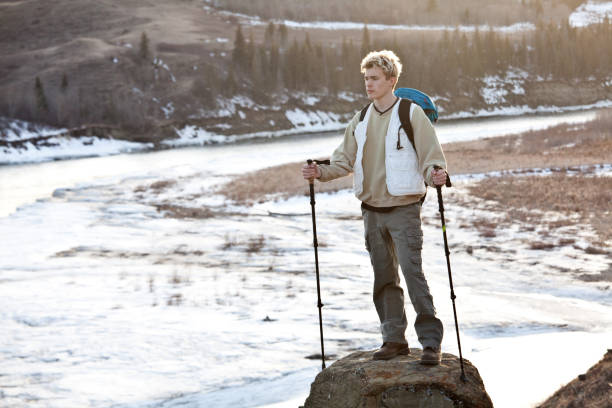 Young Male Caucasian Hiker In Winter With Backpack and Poles On Hoodoo