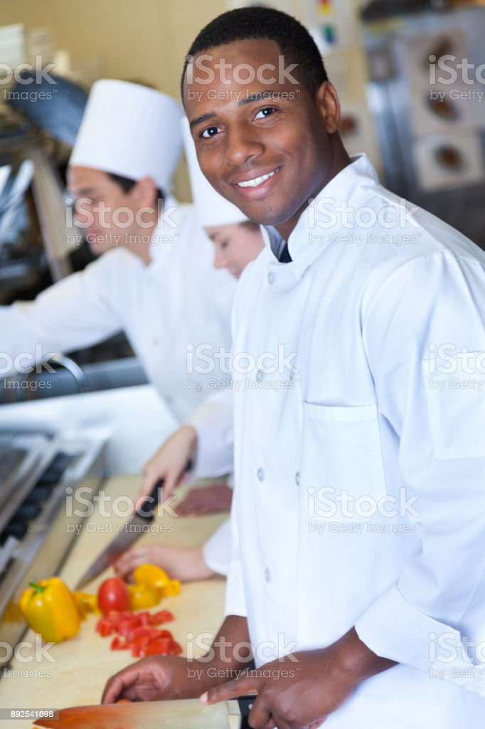 Young male chef chops vegetables in restaurant kitchen stock photo