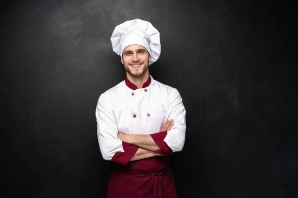 Junge männliche Koch isoliert auf schwarzem Hintergrund. – Foto