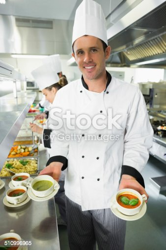 Young male chef presenting two types of soup while smiling at the camera