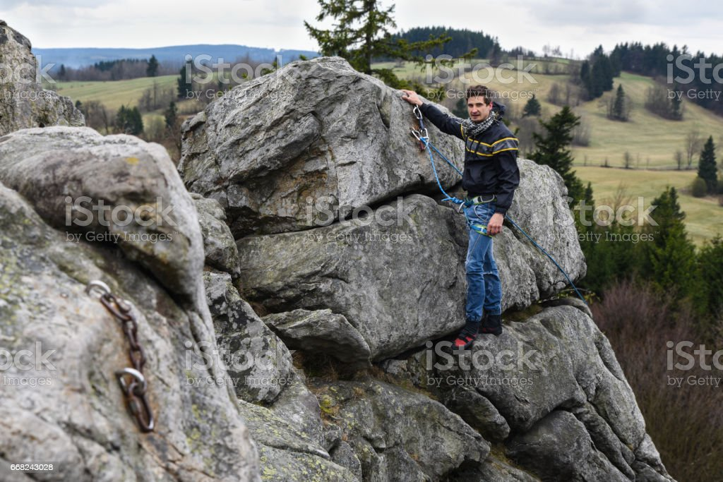 Young male climber on the top of the rock resting foto stock royalty-free
