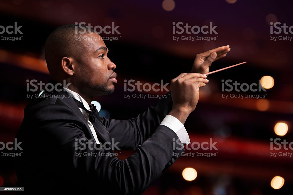 Young male conducting orchestra with his baton raised stock photo