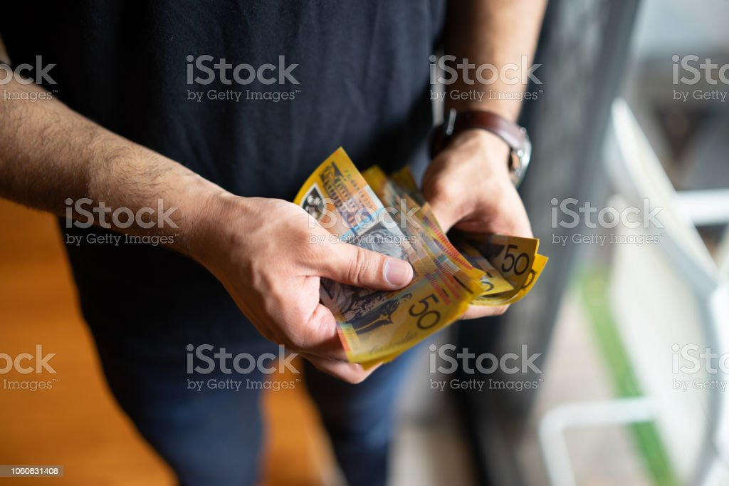 young male counting australian dollars stock photo