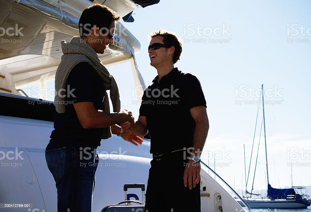Young male crew member greeting man on board yacht, smiling  25-29 Years Stock Photo