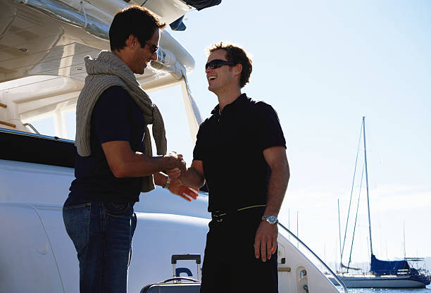 Young male crew member greeting man on board yacht, smiling stock photo