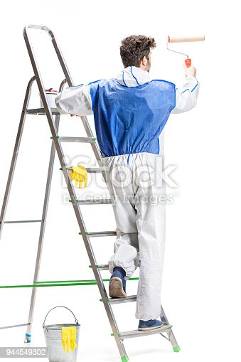 835790922 istock photo Young male decorator painting with a paint roller climbed a ladder isolated on white background 944549302