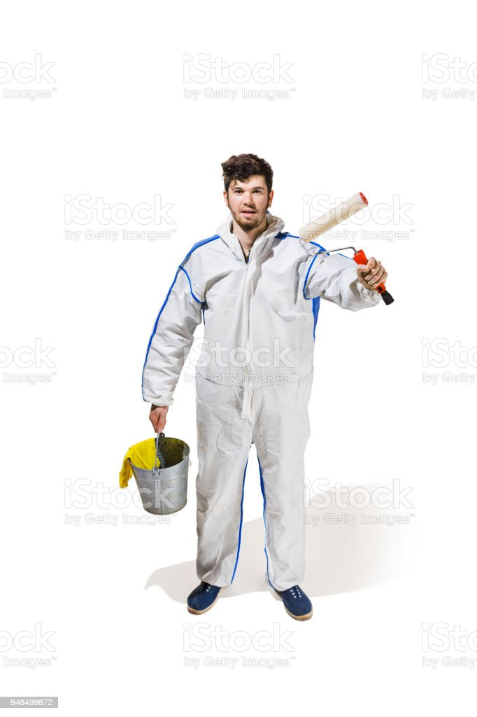 Young male decorator painting with a paint roller climbed a ladder isolated on white background stock photo