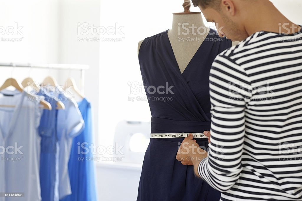 Young male designer taking measures on a mannequin stock photo