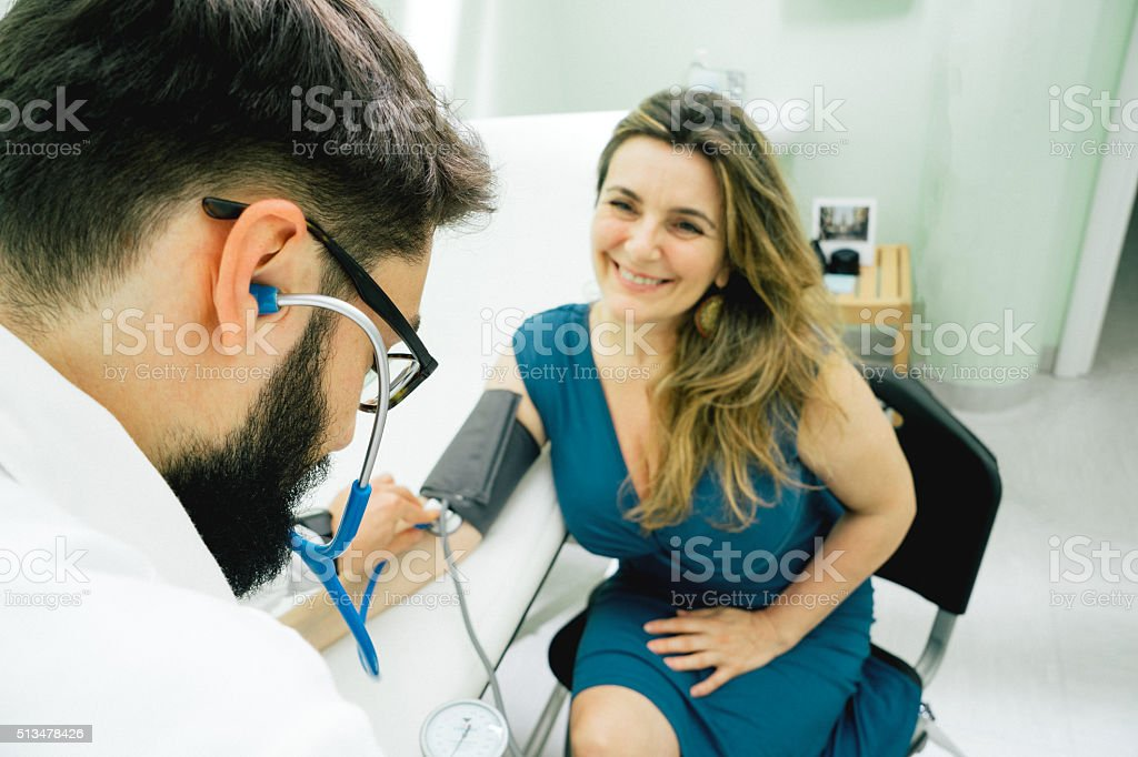 Young Male Doctor Measuring Blood Pressure stock photo