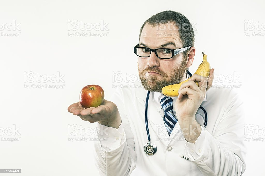 \'Nutritionist male white doctor holding banana and apple in...