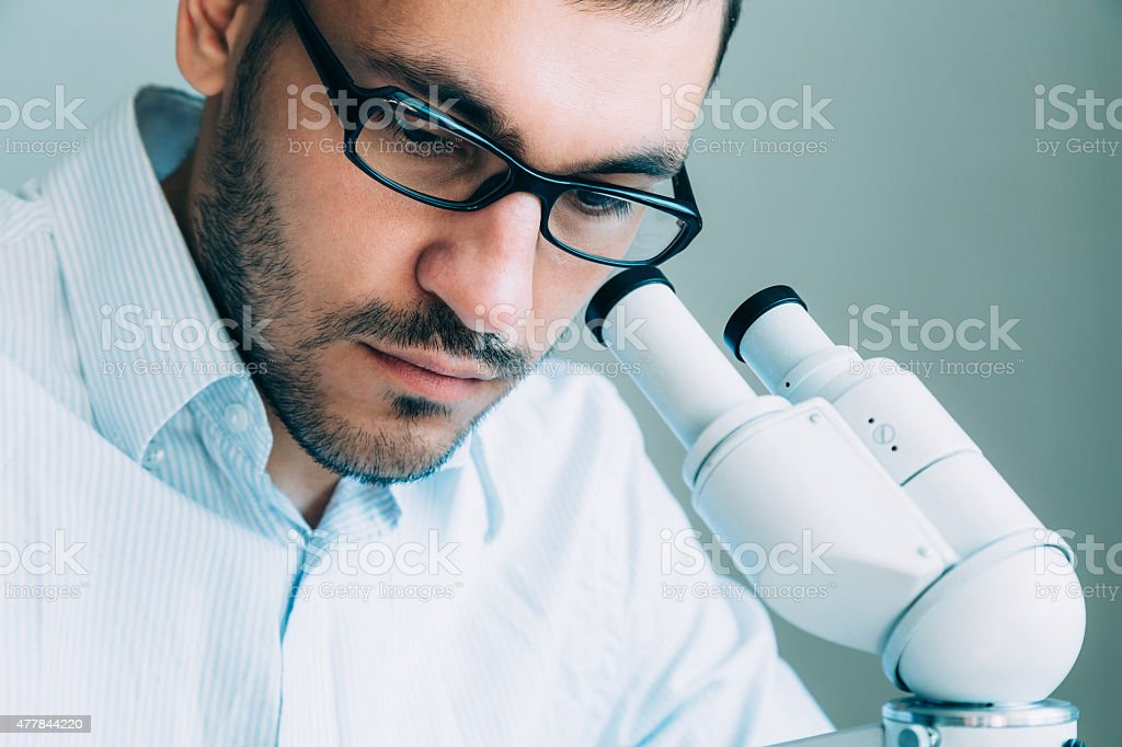 Young male doctor viewing through microscope stock photo