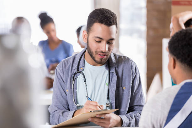 Young male doctor volunteers in free clinic Young male doctor takes notes while talking with injured African American male patient. The patient is wearing an arm sling. The doctor is volunteering in a free clinic. film and television screening stock pictures, royalty-free photos & images