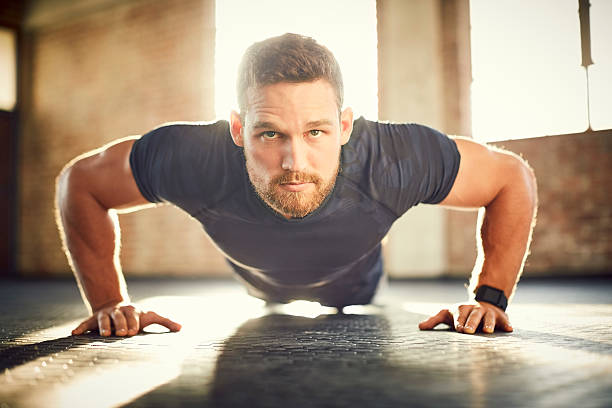 Young male doing push-ups on gym floor – Foto