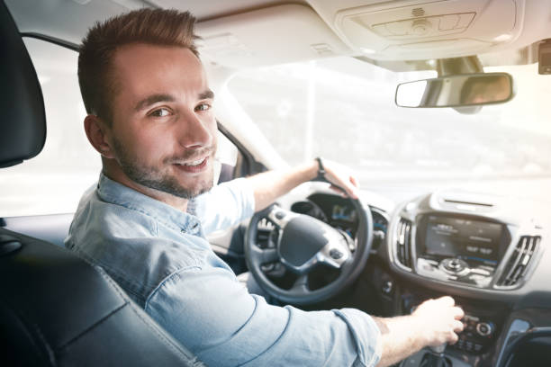 Young male driver behind the wheel stock photo