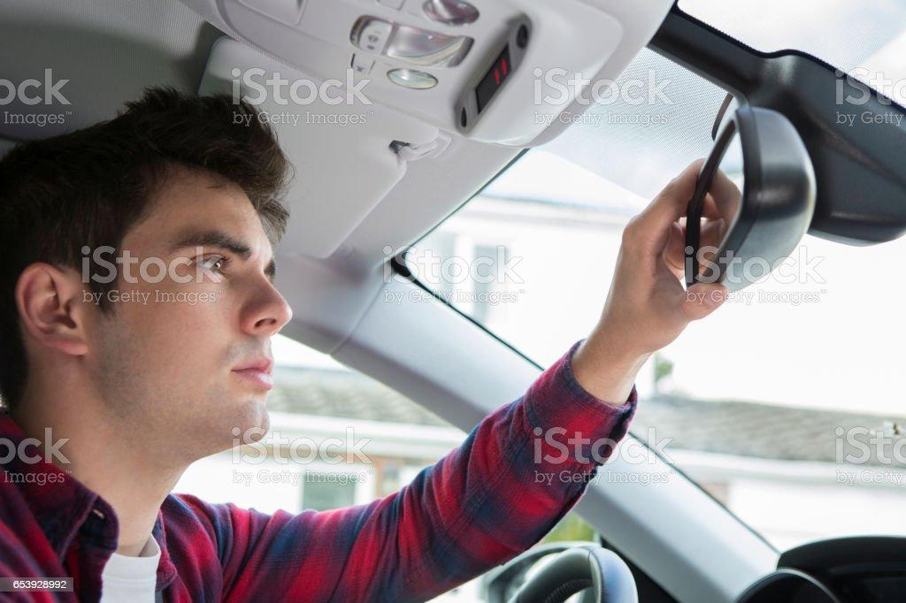 Jovem piloto masculino em verificar o espelho retrovisor de carro - foto de acervo
