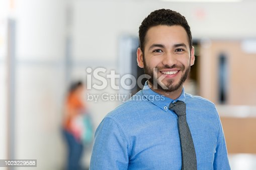 A smiling young man wears a tie as he stands in the hallway of his school building and smiles proudly for the camera.  He is a school staff member.