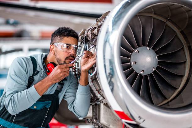 飛行機のジェット機をチェックする若い男性エンジニア - 航空整備士 ストックフォトと画像