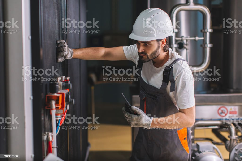 Young male engineer in factory checking nanometre royalty-free stock photo