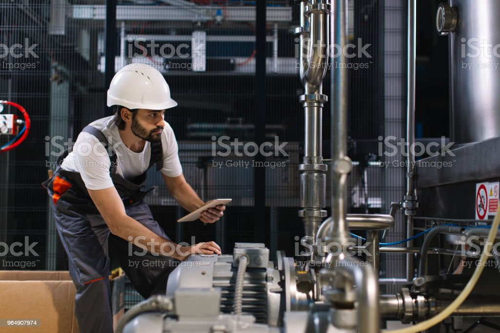 Young male engineer in factory controlling production royalty-free stock photo