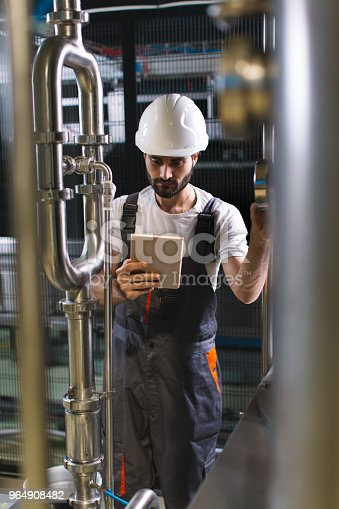 Young male engineer in factory controlling production with tablet