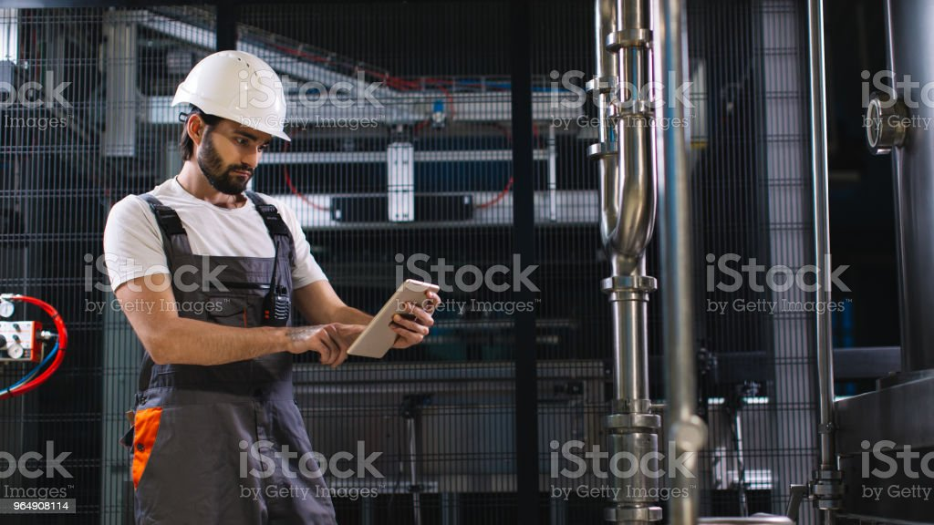 Young male engineer in factory using tablet royalty-free stock photo