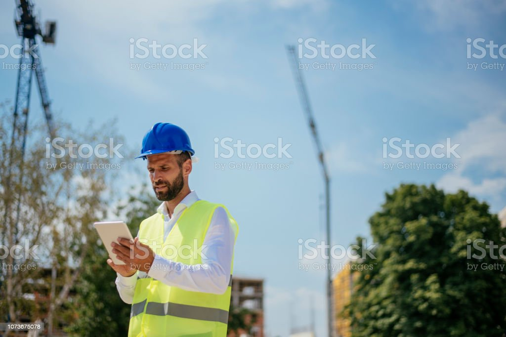Young male engineer with digital tablet. Shadow DOF. Developed from...