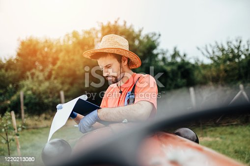 Young farmer with a hat checking and reading sowing plan and checklist before work. Agricultural concept.