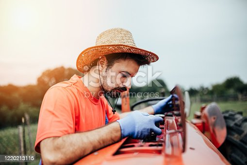 Young farmer repairing tractor engine and checks fuels and oil level