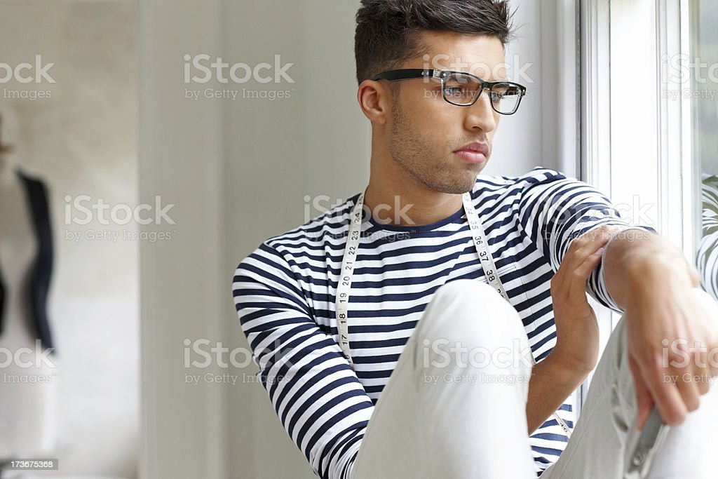 Young male fashion designer sitting by a window looking outside royalty-free stock photo
