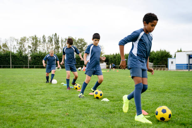 Young male footballers doing dribbling drills on field stock photo