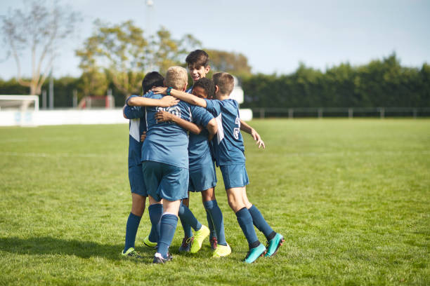 Junge männliche Fußballer in Huddled Umarmung auf dem Feld – Foto