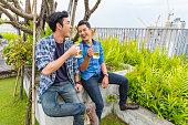 istock Young Male Friends Having Drinks at a Rooftop Party 802318378