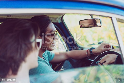 972962180istockphoto Young male friends using GPS navigation on road trip 641996318