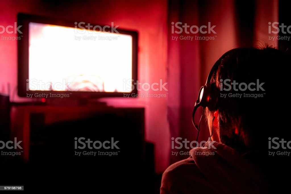Young Male Gamer With Glasses And Headset Playing Video Game At Home