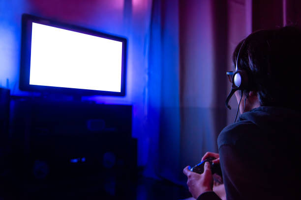 junger mann mit brille und kopfhörer spielen video-spiel zu hause in den dunklen raum mit spielkonsole controller gerade bei led tv gamer. gaming und entertainment-konzepte - lila teenschlafzimmer stock-fotos und bilder