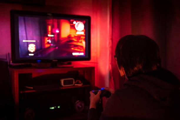 junge männchen gamer mit brille videospiel zu hause in den dunklen raum mit spielkonsole controller, led-tv anzusehen. gaming und entertainment-konzepte - lila teenschlafzimmer stock-fotos und bilder
