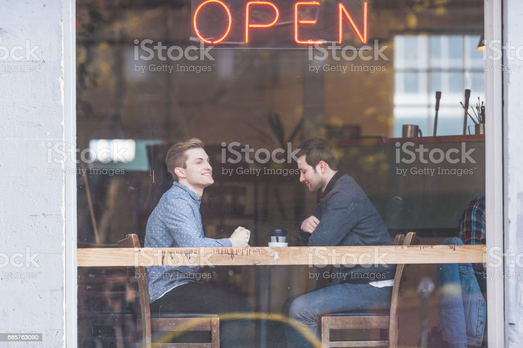 Young male gay couple enjoys beverages and conversation together in an urban coffeehouse royalty-free stock photo