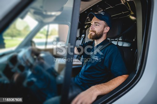 Side view of confident young independent delivery expert sitting in driver's seat of van ready to begin transport.
