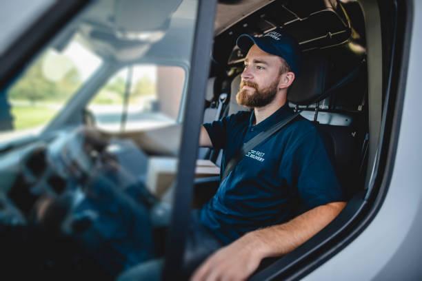 joven conductor de gig masculino esperando para comenzar en las entregas - conductor oficio fotografías e imágenes de stock