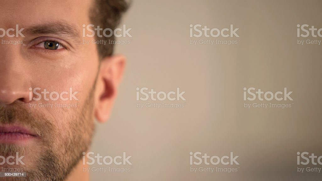 Young male half face looking into camera, average man opinion poll, statistics stock photo