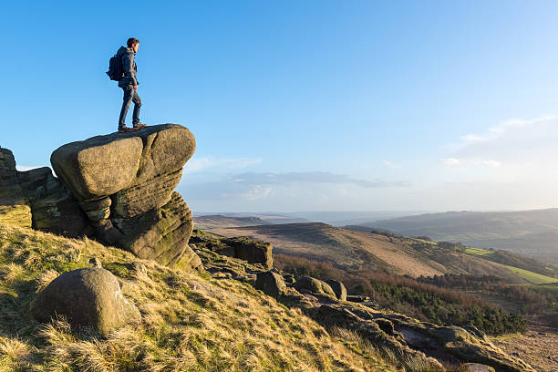 young male hiker stood on rocky outcrop - outcrop stock pictures, royalty-free photos & images