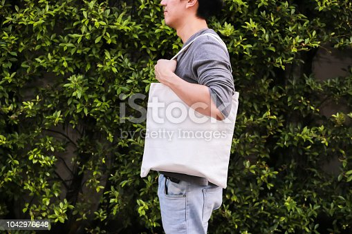 Young male hipster holding and carrying an empty blank canvas tote bag over green nature background - with copy space