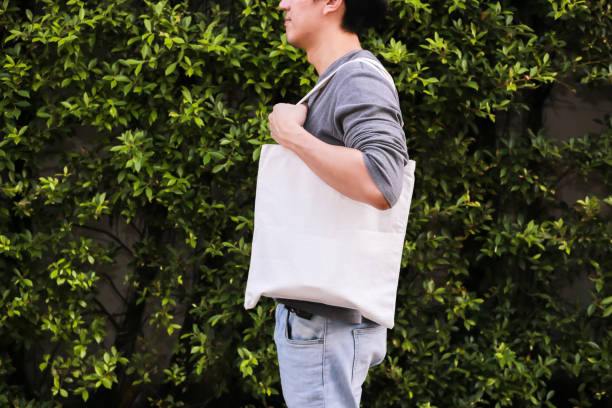 young male hipster holding and carrying an empty blank canvas tote bag over green nature background - with copy space. - tote bag imagens e fotografias de stock