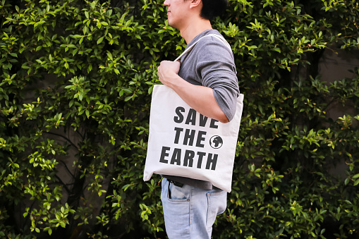 Young male hipster holding and carrying the Save The Earth tote handbag in green nature environment background - ecology and recycle concept