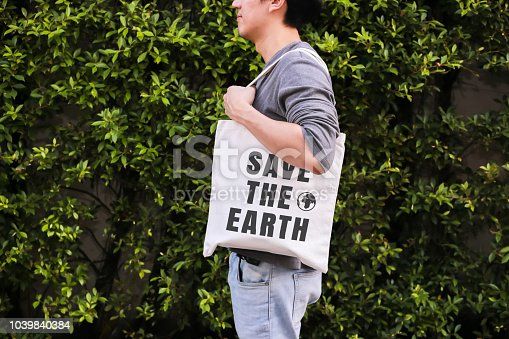 istock Young male hipster holding and carrying the Save The Earth tote handbag in green nature environment background - ecology and recycle concept. 1039840384