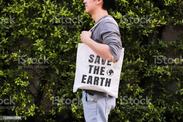 Young male hipster holding and carrying the save the earth tote in picture id1039840384?b=1&k=6&m=1039840384&s=612x612&h=cea4dnafondcr3wybg6upwgjtmsicpqdbvwhy2x7nvm=