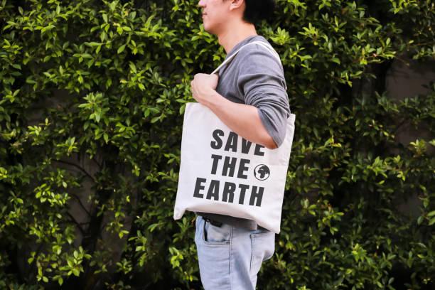 Junge männliche Hipster halten und tragen die Save The Earth tote Handtasche in grüner Natur Umwelt Hintergrund - Ökologie und Recycling Konzept. – Foto